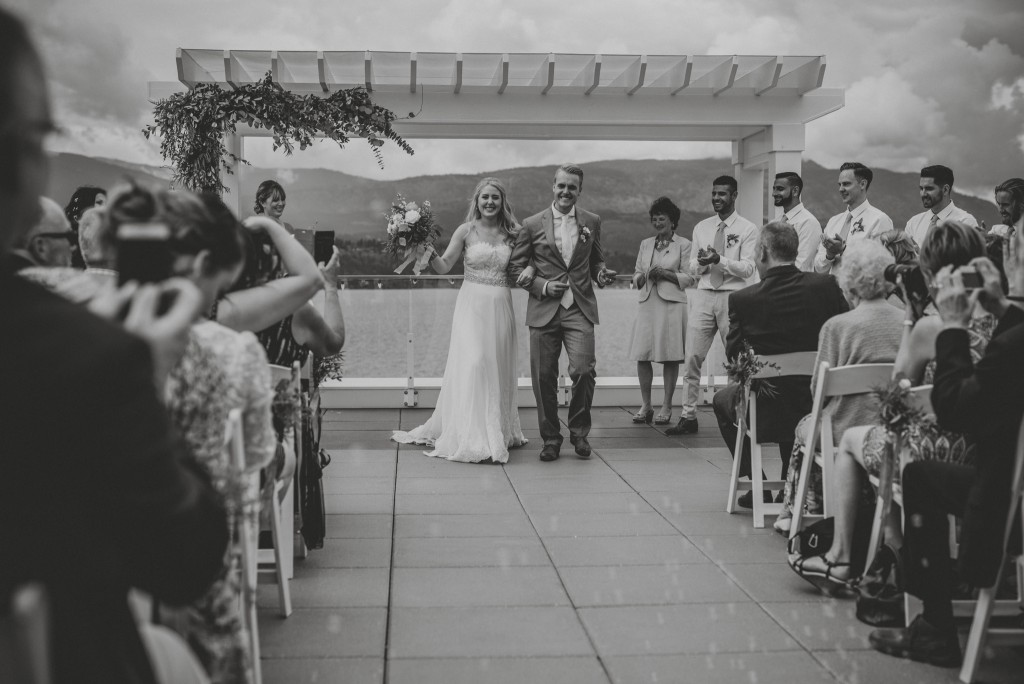 Bride and groom dancing down aisle